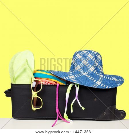 Suitcase with bikini and sunglasses.