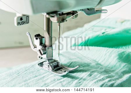 sewing machine working part with light green cloth