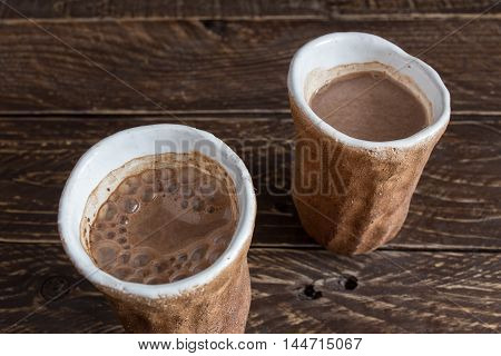 cocoa in earthen cups brown clay cups with a white stripe cocoa cups on a brown background