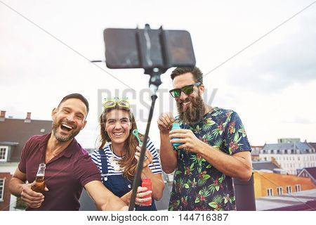 Three partying young adult friends in summer clothing taking pictures of themselves on roof while drinking beer and blowing bubbles