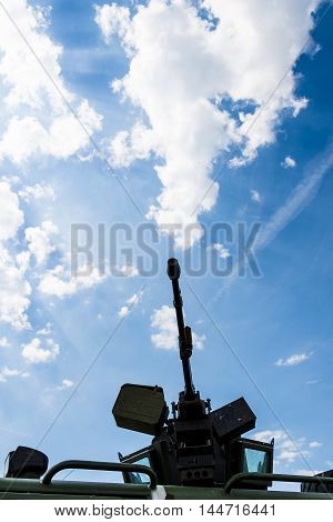 Heavy machine gun on a background of blue sky and clouds