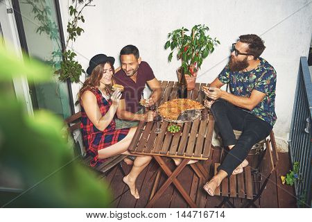 Woman in checkered dress and hat eating pizza on her small apartment porch with two male friends