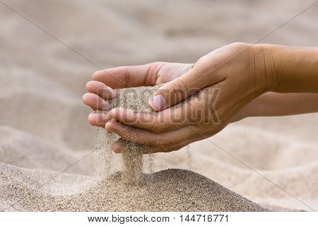 sand running through hands of woman in the beach