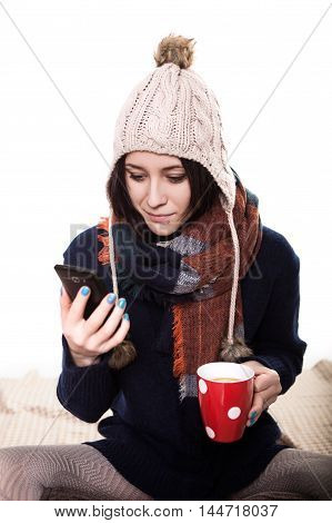 Young woman drinking coffee and talking on the mobile phone.