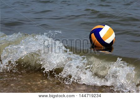 Volleyball ball in the sea with waves and splashes