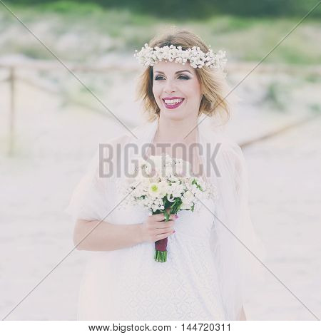 Beautiful blond fiancee in white wedding dress selective focus and square image