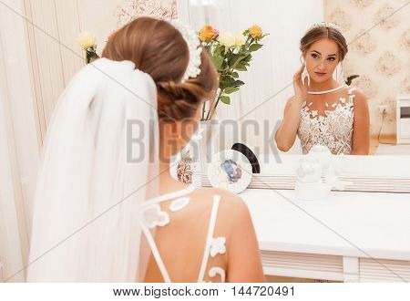 lovely bride, model preparing to wedding day in front of mirror.