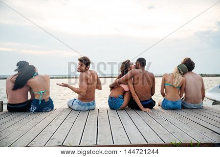 Sad confused young man sitting between happy hugging couples on pier