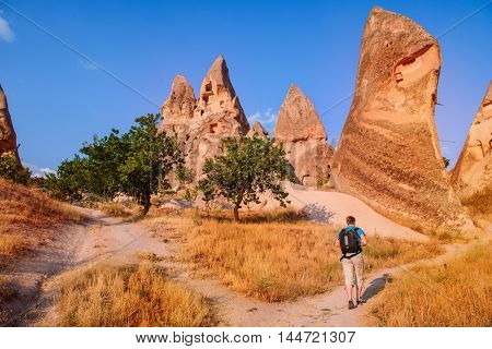 Solo backpacker hiking among the cave rocks in Cappadocia, Turkey