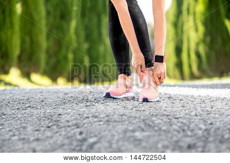 Woman lacing up sport sneakers on the gravel road.