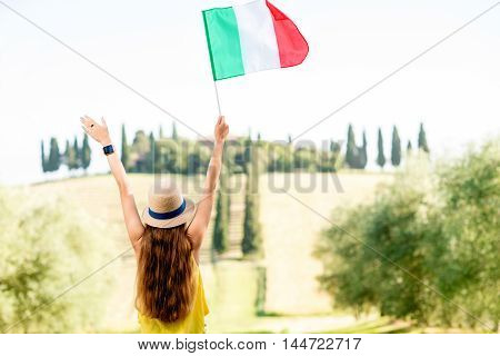 Young female traveler with Italian flag enjoying beautiful Tuscan landscape in Italy.