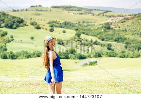 Young woman in blue dress and hat enjoying beautiful Tuscan landscape in Italy.