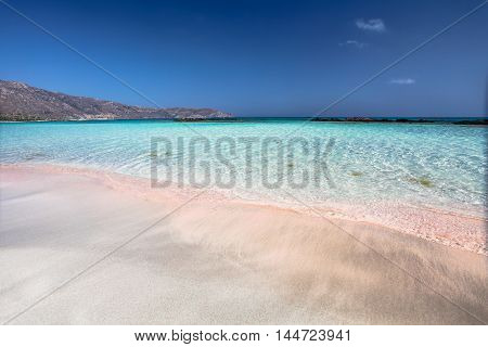 The wave of the sea on the pink sand and beautiful beach. Coast of Crete island in Greece. Pink sand beach of famous Elafonisi (or Elafonissi).