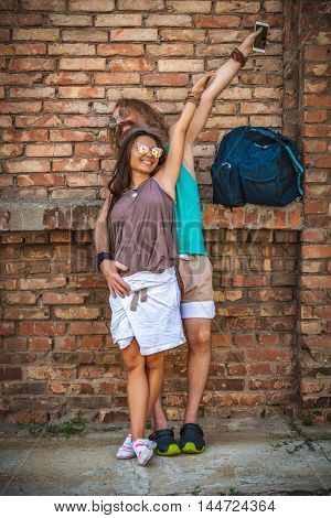 portrait of happy couple of hippie against background of a brick wall