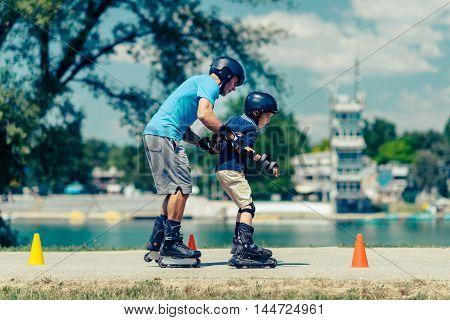 Roller skating class with senior teacher and little boy