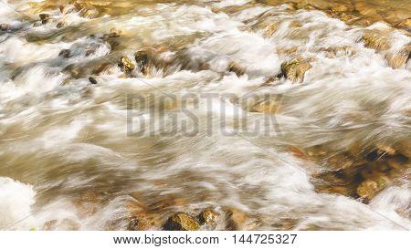 Mountain river flowing through rocks, close up