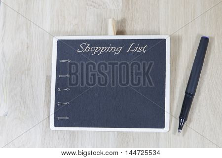 view of blackboard with the phrase shooping listtop over wooden board with pen and notebook