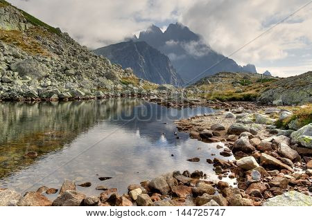 Mountain cloudy landscape. Beautiful lake among mountain peaks in High Tatra Slovakia.
