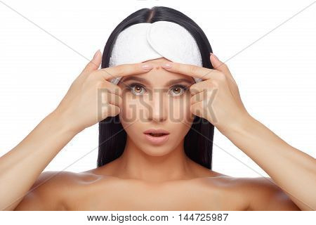 Shocked Woman Looking At Pimple On Forehead. Young Woman Squeezing her Pimple, Removing Pimple from her Face. Woman Skin Care Concept