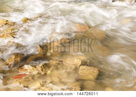 River flowing through rocks with white water rapids in long exposure, close up