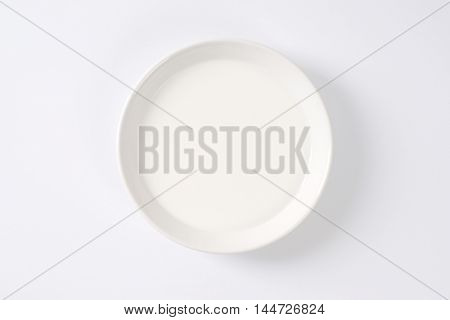 plate of fresh milk on off-white background with shadows