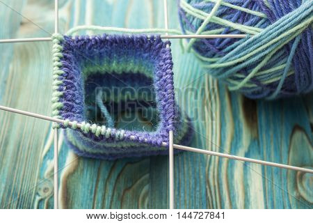 Knitting of blue and green melange wool sock with five needles on wooden rustic background. The beginning on knit cloth