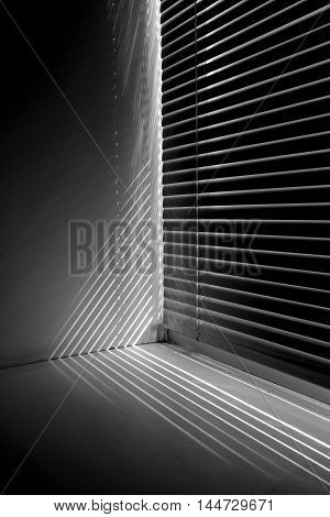 Window closed shutters and through the slot punched sun rays