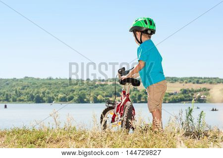 Child riding a bicycle. Child with a bicycle on the river bank. Kid in a helmet riding a bike in the forest. Beautiful baby. Toned image.
