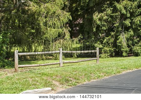 Decorative wooden fence along park asphalt alley