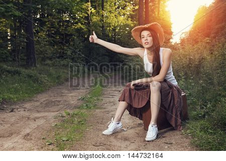 Pretty girl hitchhiking on the road