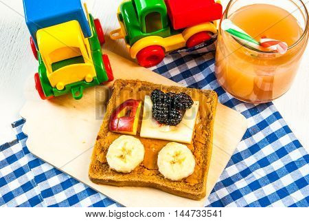 Funny breakfast for kid: a sandwich with fruit machine and peanut butter