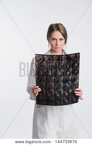 Portrait of thoughtful female doctor in the white uniform looking at the x-ray image