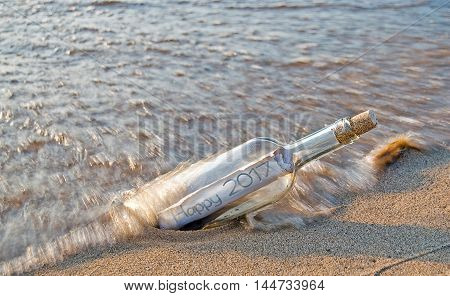 New Year 2017 message in a bottle on the beach in water.