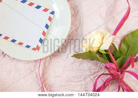 Table for romantic dinner: a plate with a note, gentle pink rose.