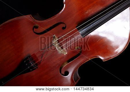 Contrabass in front of black background close up