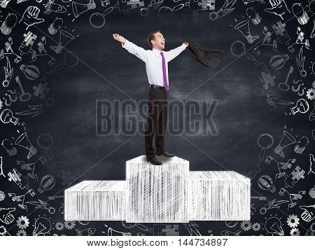 Handsome businessman celebrating victory on abstract podium sketch with business icon drawings around. Blackboard background. Winner concept