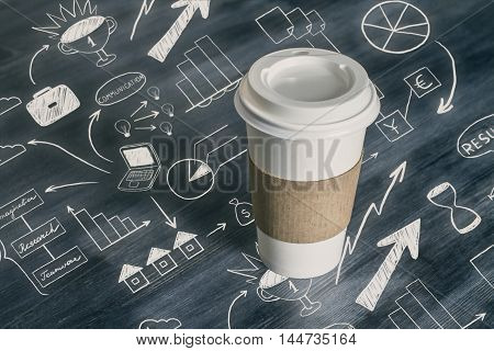 Closeup of takeaway coffee cup on wooden desktop with business drawings