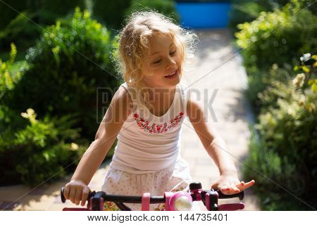 Beautiful little girl on a bicycle in the park, summer outdoor.