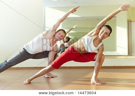 Image of young sporty girl and guy doing physical exercise