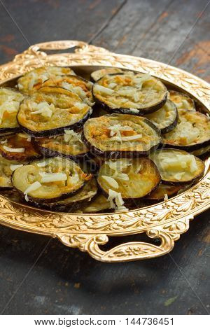 fried eggplant with garlic in vintage golden dish on an old black wooden table closeup