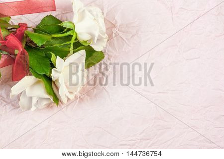 Tender pink roses on a pink textured paper background. Romantic mood.. Copy space