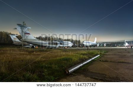 Parking older passenger aircraft at night on a background of forest and stars