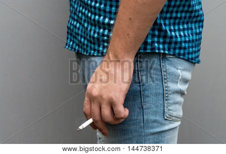 A man in a plaid shirt and blue jeans with a cigarette in his hand.
