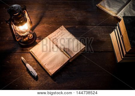 Old-fashioned kerosene lamp and copybook on the dark table in twilight. Soft focus