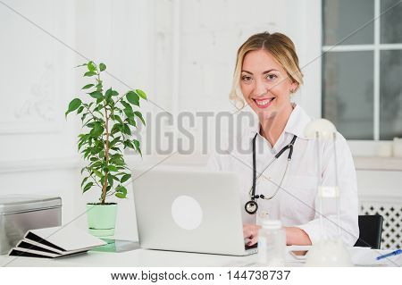 Portrait Of Happy Young Female Doctor Working On Computer.
