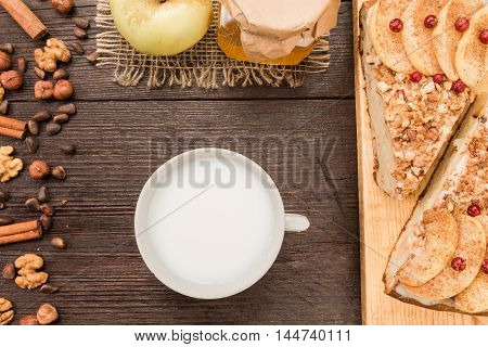 Cup of milk and homemade pie covered with apples, cinnamon, foxberry and nuts on the dark wood table