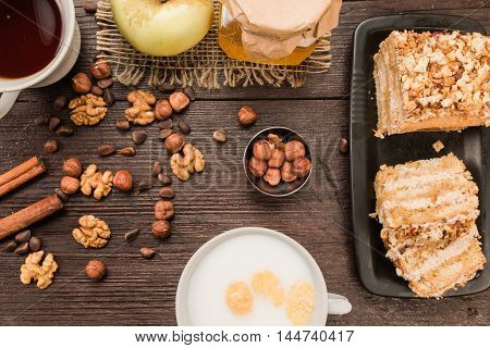 Homemade nut cake with chocolate cream, various nuts, tea and milk on dark wood surface