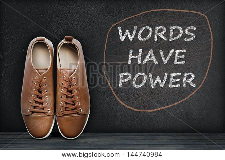 Words have power text on black board and shoes