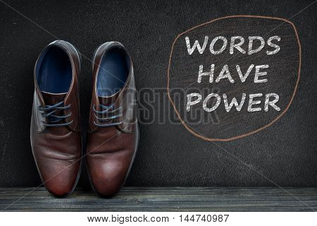 Words have power text on black board and business shoes on wooden floor