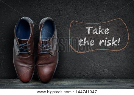 Take the risk text on black board and business shoes on wooden floor